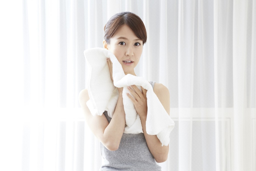 洗顔後に顔を拭く女性