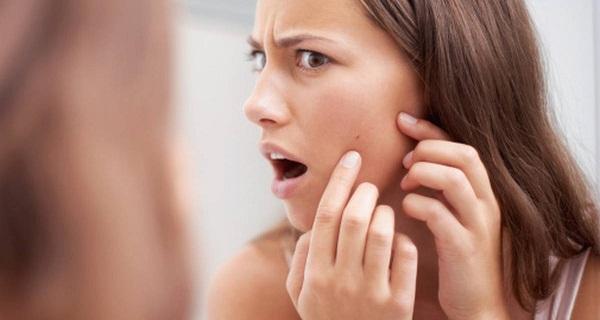 頬ニキビを見つける女性