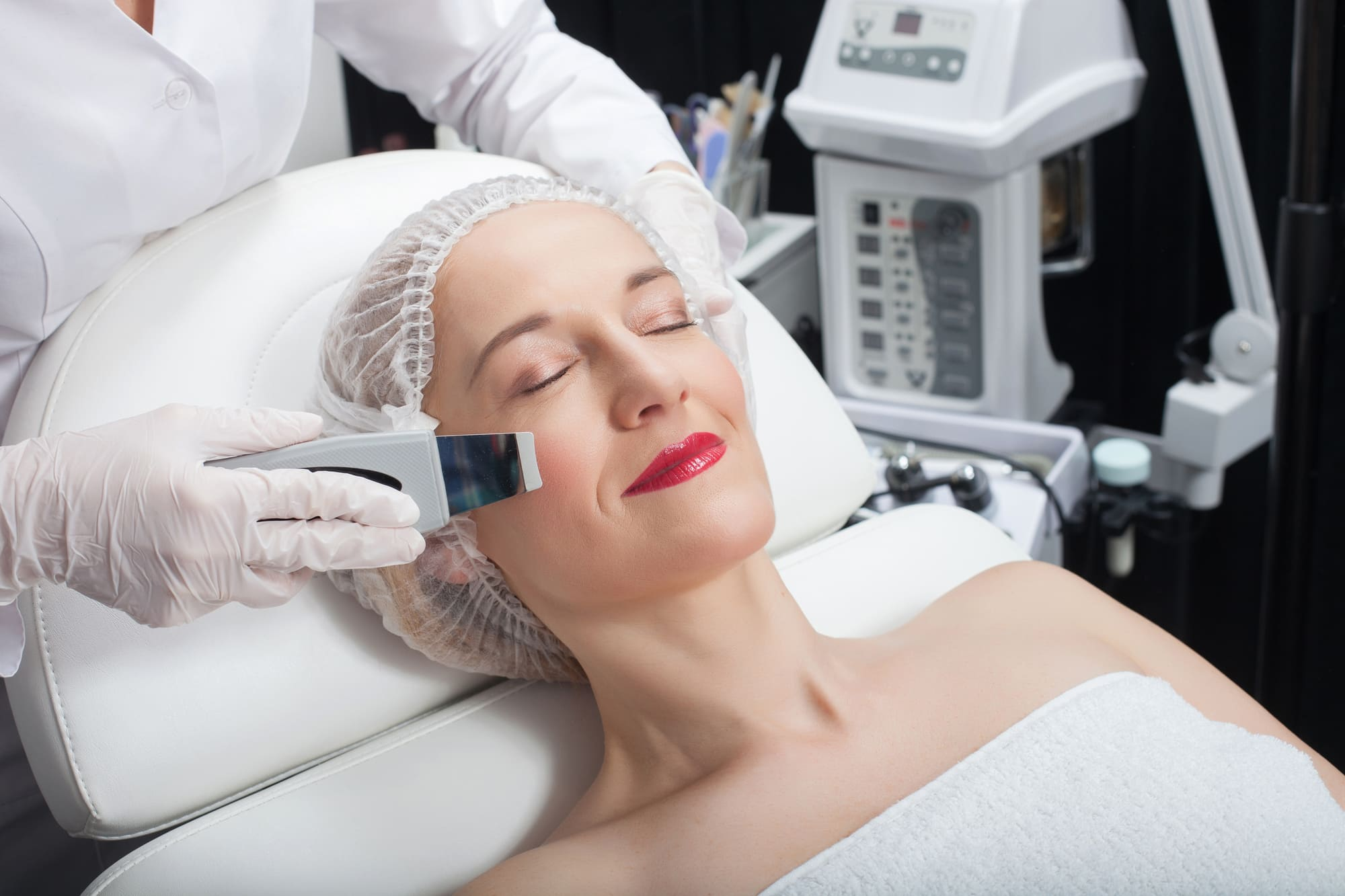 Close up of arms of beautician making laser treatment on female face. The woman is lying and smiling. Her eyes are closed with pleasure